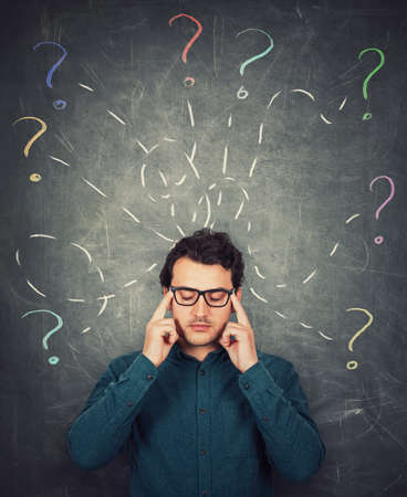 Focused businessman keeps fingers to his temples, eyes closed. Business worker concentrate his thoughts to answer multiple questions as colorful interrogation marks around head.