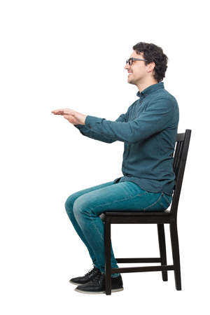Side view full length portrait of cheerful casual man seated on a chair keeps arms outstretched ahead for a medical control isolated over white background with copy space. People health examination.