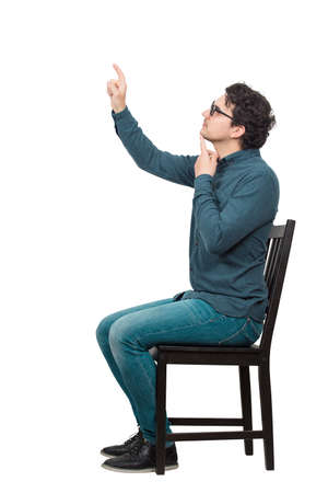 Side view full length portrait of thoughtful businessman sitting on chair hand under chin, pressing an invisible object or screen with his index finger isolated on white background with copy space. Banco de Imagens