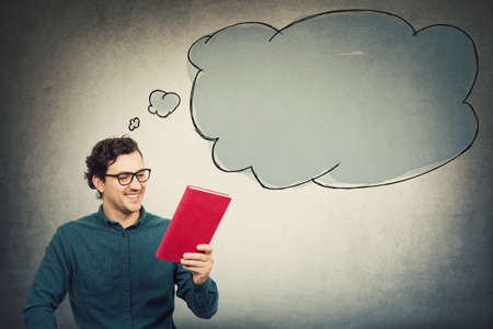 Happy young man, student guy, holding an interesting red book, reading the textbook title. Education concept, learning process. Guy choose what to read. Empty thought bubble comes out of his head.