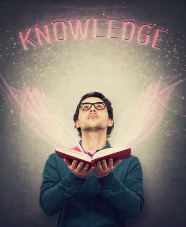 Young man, student or teacher, holds an open bewitched book in his hands, looking up cheerful as magic lights creates the text knowledge over head. Education concept, learning process. Banco de Imagens