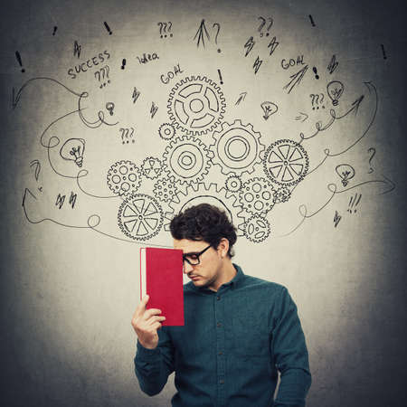 Tired student guy, holds a book, looks down with pessimistic emotion. Man pondering, focuses his mind, thinking of solutions to solve the task. Gear cogwheels and arrows as thoughts around head.