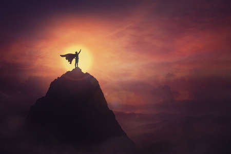 Conceptual sunset scene, superhero with cape standing brave on top of a mountain looks determined at horizon raising one hand up as a winning leader. Hero power and motivation, overcoming obstacles. Banco de Imagens