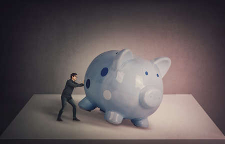 Surreal business concept, tiny businessman trying to push a huge piggybank out of the table, to get something out of it. Breaking the piggy money bank to spend all the savings. Finance and economics.