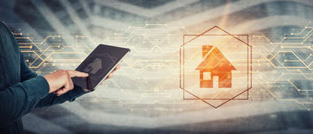 Working and studying from home conceptual background. Close up person hands using tablet computer gadget, press the PC screen to display a digital house symbol. Modern technology and education concept