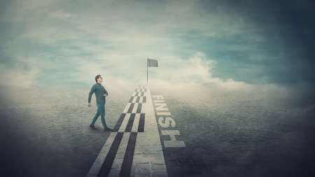 Conceptual scene, confident and competitive businessman crossing the finish line, obtain victory and become the competition winner. Challenge winning, motivation, success and self development.