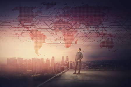 Conceptual sunset scene with a businessman on the rooftop watching confident over the city horizon. Digital world map exposed on the sky as global communication symbol. Crypto technology connection.