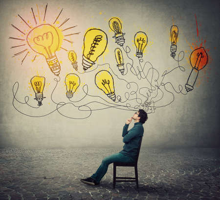 Businessman sitting on chair, keeps hand under chin, thoughtful gesture, looking up with interest, thinking of new ideas as multiple light bulbs come out of his head. Business employee planning work.