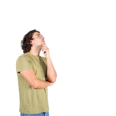 Side view portrait of pensive young man, long curly hair style, keeps hand under chin, looking up thoughtful gesture, isolated over white background with copy space. Focused casual guy thinking.