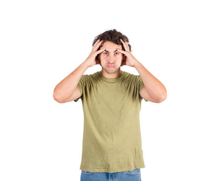 Portrait of tired and annoyed young man, long curly hair style, holding his head with hands, looking exhausted and frustrated. Displeased casual guy blowing cheeks isolated on white background.
