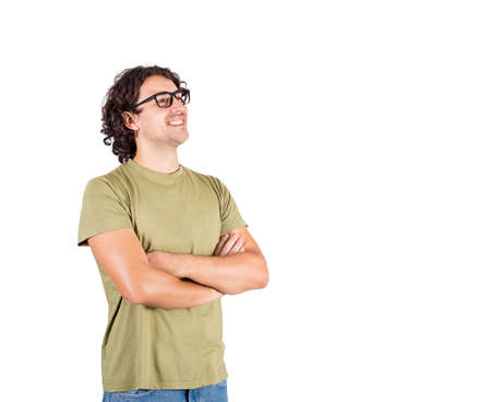 Portrait of happy brunette young man, long curly hair wears glasses, keeps arms folded looking confident aside isolated on white background. Cheerful and positive casual caucasian guy smiling.
