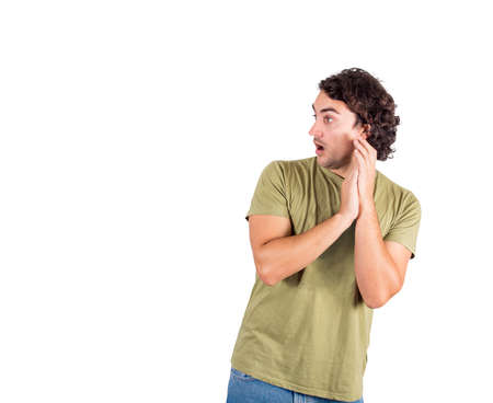 Portrait of surprised and shocked young man, long curly hair style, big eyes looks aside astonished isolated on white background with copy space. Amazed guy, funny open mouth expression staring away.