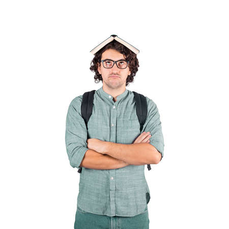 Portrait of perplexed student guy arms crossed, holding a book over head, looks tired of constant learning. Young brunette man with long curly hairstyle wears eyeglasses isolated on white background.