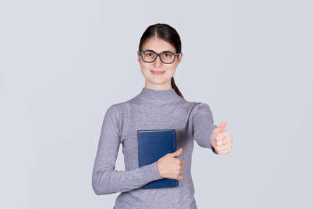 Young student girl holding book and showing thumb up, isolated on a white background. Фото со стока