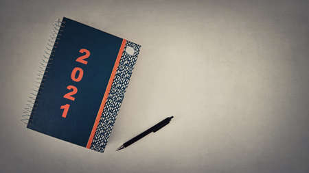Goals notepad for the 2021 New Year. High angle shot of a spiral notebook and pen on the office desk with copy space. The list of plans and purposes for the coming season. Simple business accessories Foto de archivo