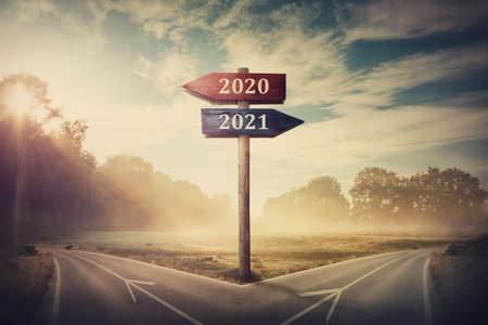 Surreal scene with a split road and signpost arrows showing two different courses, left and right, past and future, old 2020 and the new 2021 year direction to choose. Life decision, choice concept. Foto de archivo