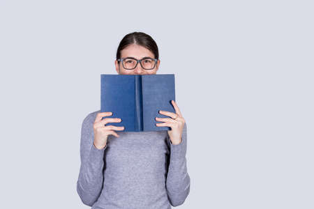 Happy student girl with glasses smiling covering half face with a opened blue book. Book lover. Ready to study hard.