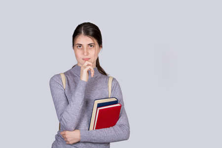 Thoughtful student girl portrait holding textbooks looking puzzled, hand under chin, isolated over white background. Serious Student girl prepared for exams, thinking of ides and planning. Foto de archivo