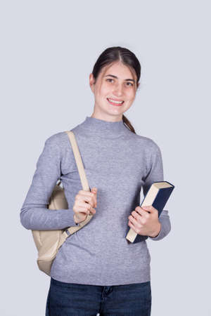 Confident student girl smiling holding one books and carrying her backpack. Cheerful student girl with positive face expression isolated on white background. Foto de archivo