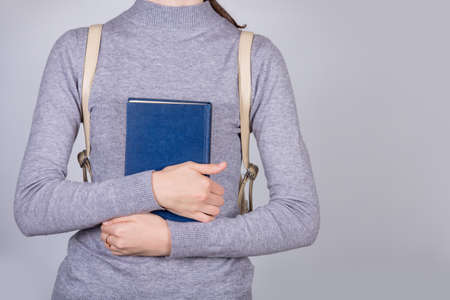 Confident smart student girl holding book iover white background. Close up of student hand holding book .Confident studying concept.