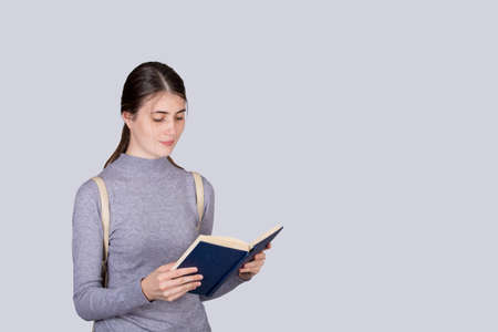 Portrait of contented girl enjoys reading a book, carrying his college backpack on shoulders. Young student girl ready for exams and session.