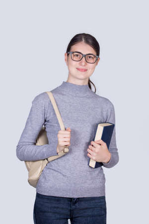 Confident student girl holding one books and carrying her backpack. Cheerful student girl with positive face expression isolated on white background.