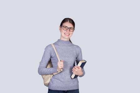 Confident student girl going to school holding one books and carrying her backpack. Cheerful student girl with positive face expression isolated on white background.