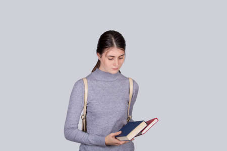 Desperate student girl holding books having anxiety, distress depression feeling, seated alone. Mess in head, anxiety and headache feeling.