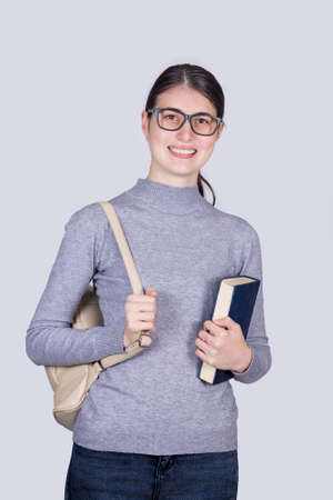 Confident student girl smiling holding one books and carrying her backpack. Cheerful student girl with positive face expression isolated on white background. Фото со стока
