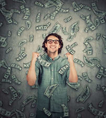 Contented young man keeps fists tight raised up as money are falling like a dollar rain. Surprised grateful guy celebrate positive expression. Lottery win, unexpected success, wealth and luck concept.