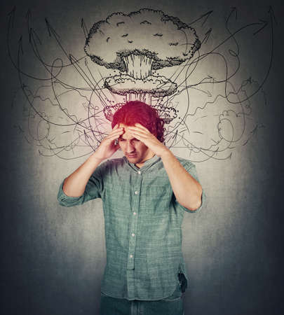 Bewildered man head explosion concept. Guy suffering headache, hands to forehead, looking down depressed. People mental health concept. Stress causes migraine and anxiety problems, dementia disease.