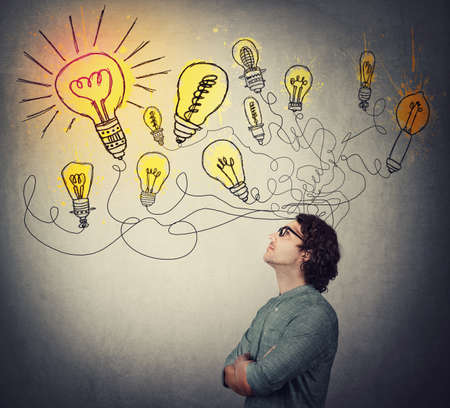 Creative businessman, thinking of great ideas, looking at bright lightbulbs on the wall. Business worker search for solutions to solve the problems, genius planning concept. Smart and ingenious guy.