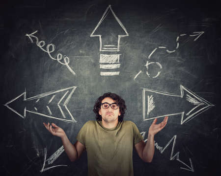 Perplexed man, hands outstretched, shrugging shoulders, has a problem with direction choice. Multiple different arrows sketches on the blackboard pointing opposed trajectories. Doubt decision concept