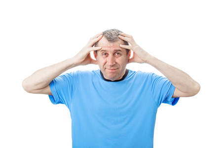 Middle aged man suffering emotional breakdown and depression isolated on white background. Middle aged man holding his head with hands, looking exhausted and frustrated.