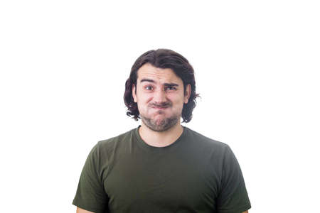 Portrait of bewildered and annoyed young man, long curly hair, looking baffled and frustrated to camera, blowing his cheeks, frowning and making perplexed grimace. Displeased guy isolated on white Stock Photo