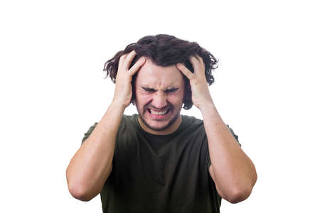 Frustrated, mad young man messing up and pulling his hair, hands to head, eyes closed screaming and clenching teeth isolated on white. Stressed guy negative emotions, suffering and looking displeased