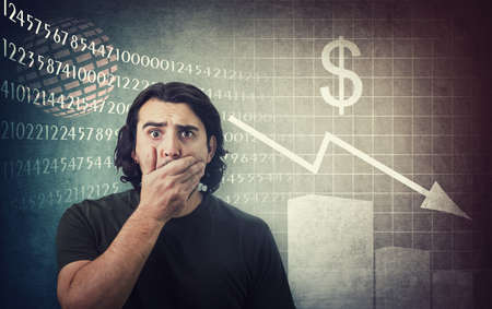 Shocked man, staring big eyes, covers his mouth with hand. Amazed and frightened due recession. Economic crisis concept, stock market financial graphs decrease.  causes business cessation Фото со стока