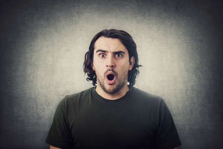 Portrait of shocked young man, long curly hair style, staring with big eyes and mouth open isolated on gray wall background. Amazed guy, astonished expression.