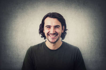 Portrait of smiling brunette young man, long curly hair style, looking joyful and laughing to camera isolated on gray wall background. Cheerful and successful caucasian guy, casual lifestyle model.