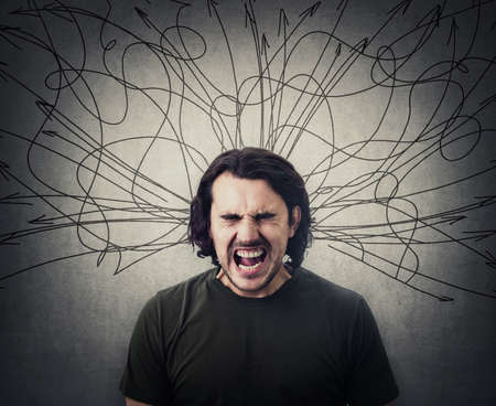 Angry and frustrated man screaming and yelling, eyes closed. Mess lines and curves sketch comes out of his head as negative emotions. Annoyed facial expression. Furious guy shouting with loud voice
