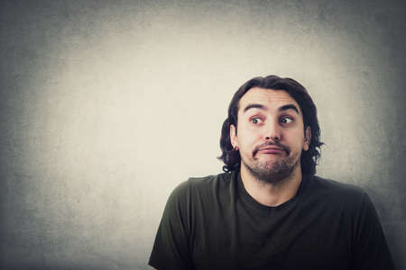 Portrait of naughty young man depicts innocent, funny face expression, looking aside, rolling eyes and hiding his glance isolated on gray wall background with copy space. Casual guy pretends no guilt