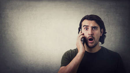 Shocked young man, during a mobile phone conversation, staring with big eyes and mouth open isolated on gray wall background, with copy space. Amazed guy hears bad news speaking on cellphone