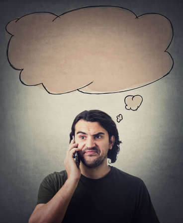 Frustrated man during a phone conversation, makes a dissatisfied expression. Empty thought bubble, thinking cloud, above his head. Disappointed guy hears bad news talking on cellphone, negative face