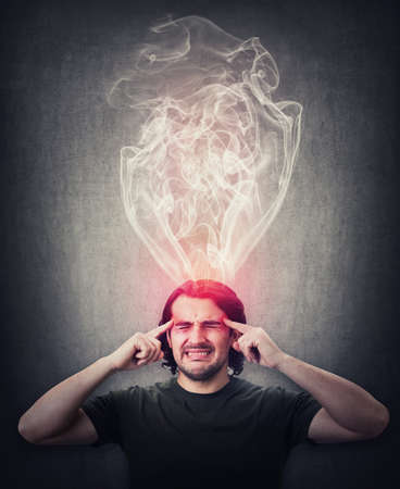 Fatigue and annoyed man, keeps fingers to his temples, feels like mind is boiling as dense steam comes out of his head. Brain burning and mental explosion with smoke due fever, anxiety and migraine