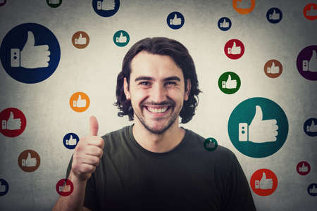 Excited young man, shows thumb up gesture, smiling contented to camera, surrounded by multicolor like signs. Casual guy, curly hair gives approval symbol, positive feedback, marketing concept