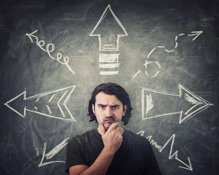 Skeptical guy thoughtful looking to camera, keeps hand under chin, puzzled suspicious expression, has to choose a direction from different arrows pointing opposite trajectories. Doubt decision concept