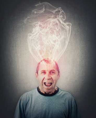 Angry middle aged man screaming and yelling, mind is boiling as dense steam comes out of his head. Fatigue and annoyed senior male, rage emotion. Dementia, brain burning, mental explosion with smoke Фото со стока