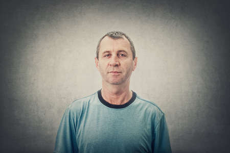 Portrait of a middle-aged man, looking to camera, against a gray wall background. Serious expression of mature middle age male front view. Фото со стока