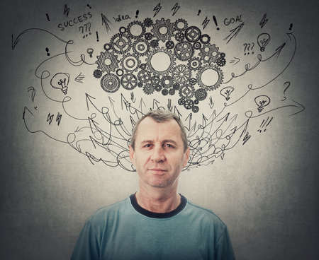Confident middle aged man, brainstorming concept, has a cogwheel brain above head. Senior male mental health, positive thinking and psychological development symbol