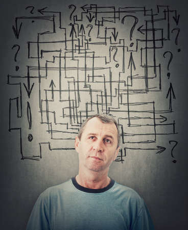 Thoughtful middle aged man, looking up pensive. Senior male thinking of ideas and solution to solve problems, planning concept. Person try to resolve the maze in his mind